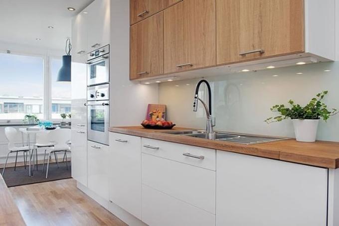 厨房以实木橱柜与台面配上白色底板,看起来十分的亮丽朴素且干净,物品也很整洁。