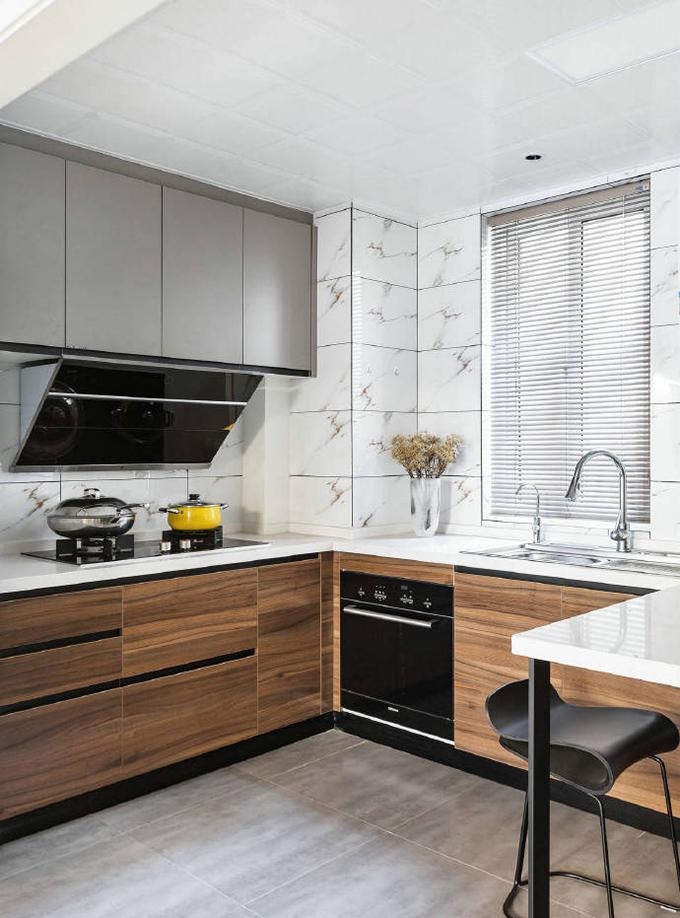 再单看厨房,墙面的装饰以白色的花纹的瓷砖为主,下面则以实木橱柜来表现,看起来十分的时尚清新。