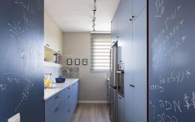 厨房以蓝色为基调,依然以百叶窗来作为装饰,避免了光线太强的尴尬,直 线型的厨房十分适合面积小的空间,进门处以黑板来装饰,很有个性。