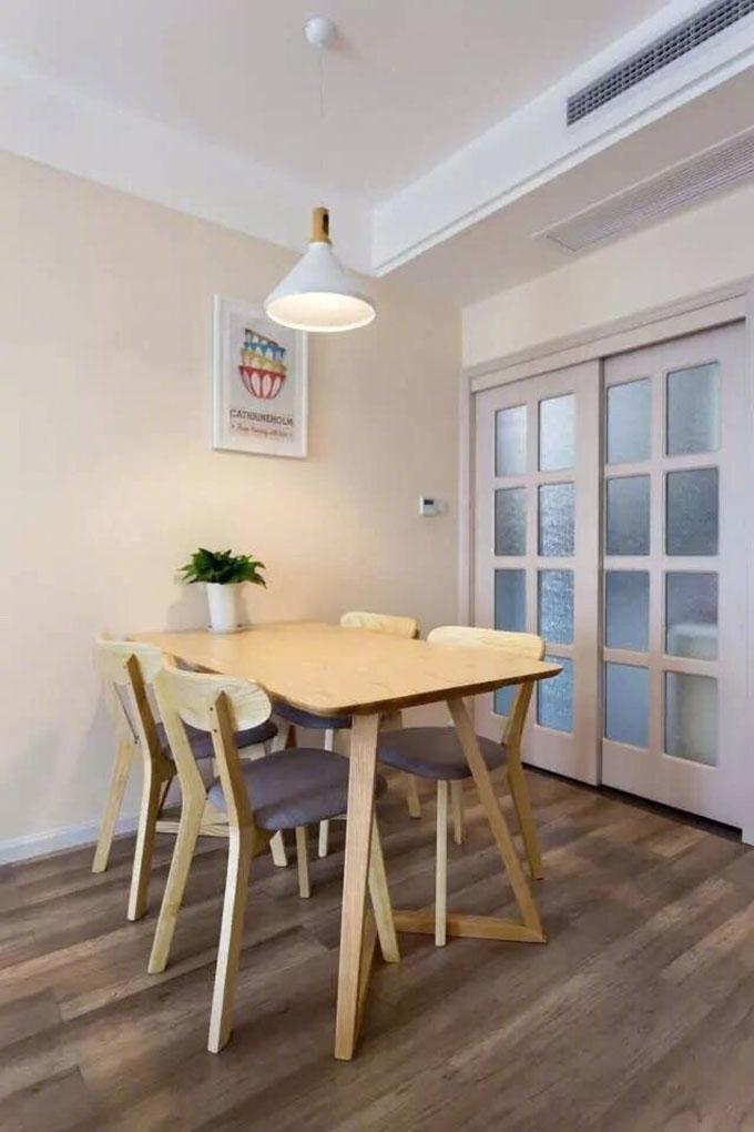而餐厅与厨房的隔断则以白框推拉玻璃门的形式来呈现,简洁的吊顶直线拉长下来,让空间显得和谐而又自然。