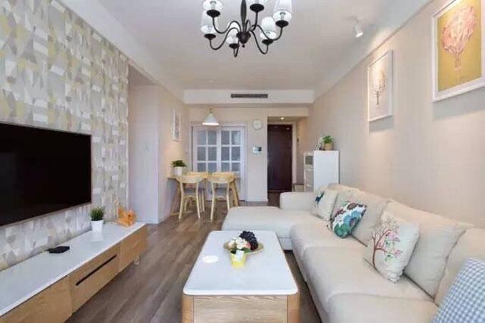 客厅沙发背景以两幅色彩简约图案清新的挂画为背景,而电视的背景以浅色调的几何来体现,其它家具均以原木来呈现。
