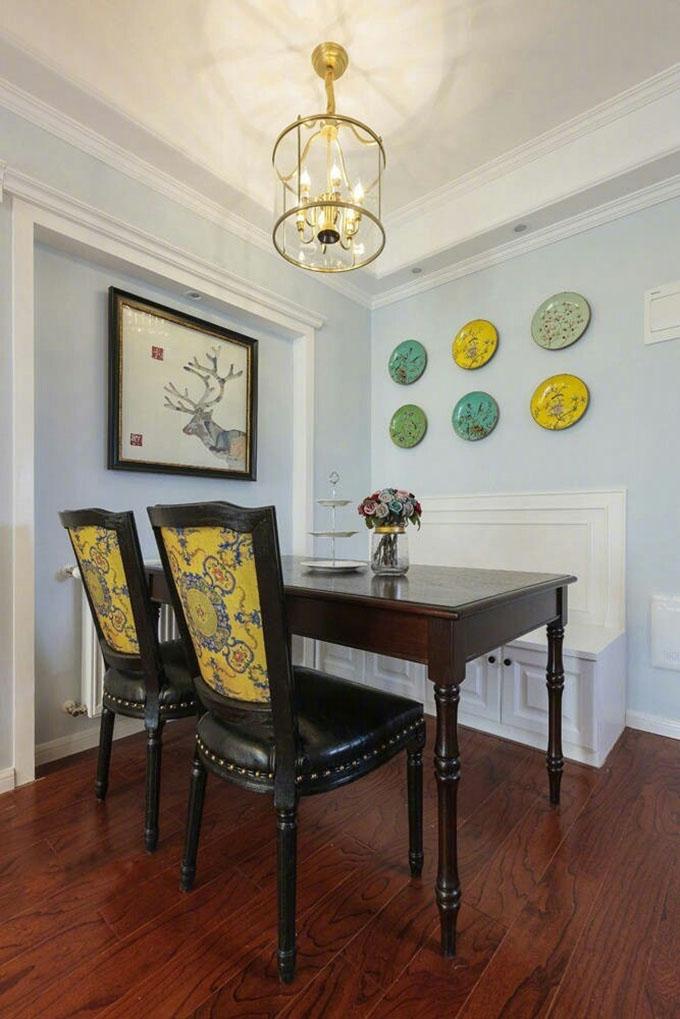 餐厅墙面以浅蓝色为主,高雅的金黄色吊灯与墙面的装饰互相呼应,成为亮点,简洁的挂画显得空间十分清新自然。