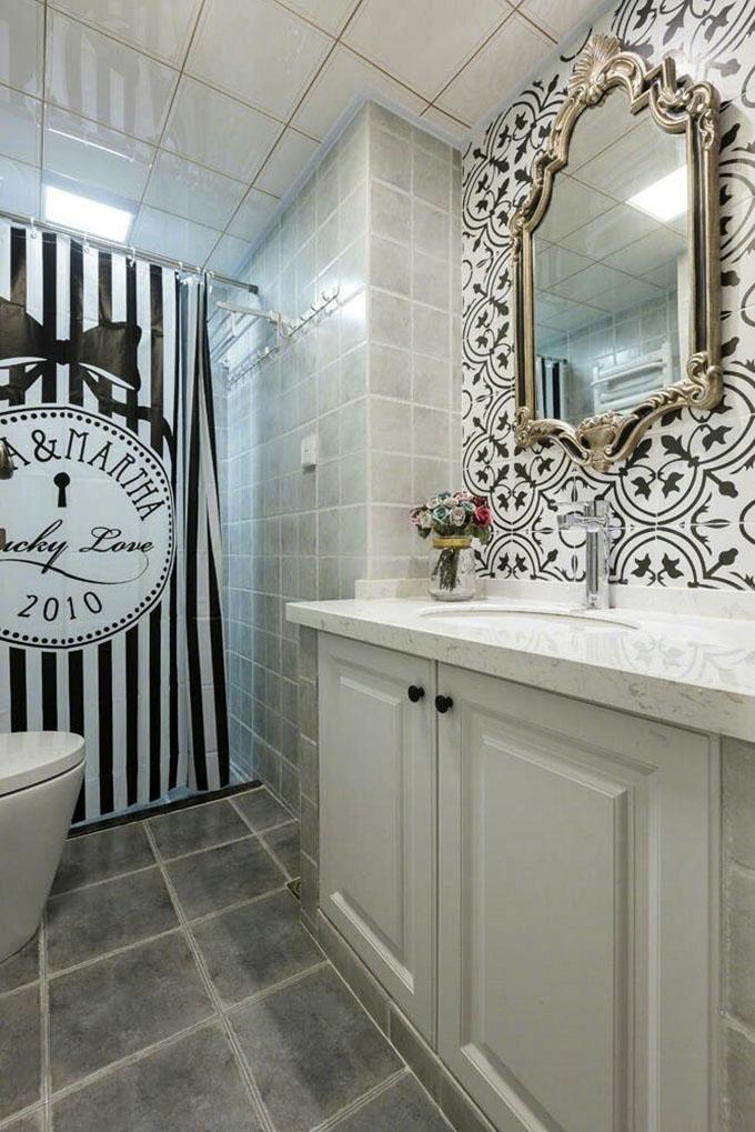 卫生间浅色的水泥灰的瓷砖显得整体空间十分的清新整洁,而挂钟式的浴帘也完美的将两个区域隔开,镜子墙面的黑白花纹也与之呼应。