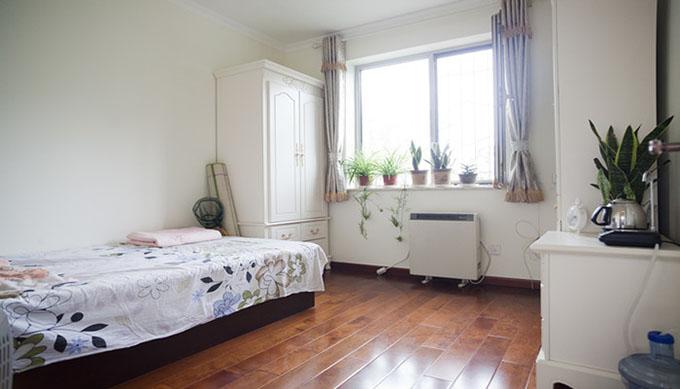 简约装修方式,地板的颜色与床颜色对称,现代化衣柜和墙壁融为一体,绿色的植物的出现空间有春色。