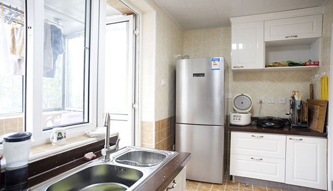 玻璃门隔离阳台,深黄色的地砖与淡色墙砖匹配呈现秋分季节,灶台与水池隔过道隔离突显厨房整洁。