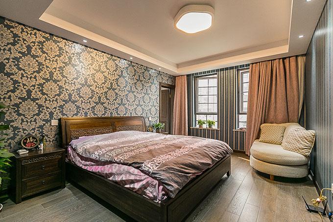 主卧采取素雅墙纸、深色复古地板、实木家具,配搭了暖色灯光打造出卧室的温暖,而且实施了隔房设计打造独立的衣帽间,呈现出空间闲暇。